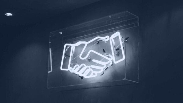 neon light of two hands shaking
